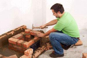 mason hammering bricks